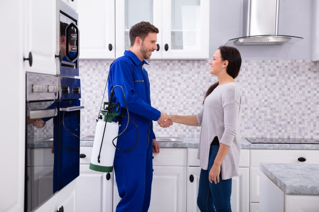 Pest Control Worker Shaking Hands With Woman